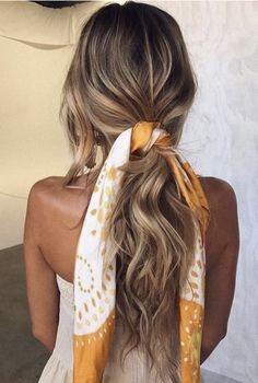 How to wear scarves as hair accessories: have you're hair in a low ponytail and tie a scarve around it, a new take on an old look.
