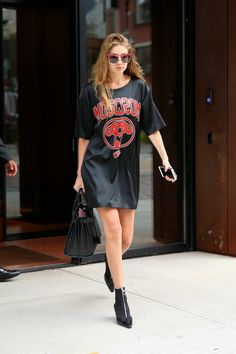 In a t-shirt dress by Moschino, oversized red sunglasses, Saint Laurent crocodile tote bag and zip-up sock boots while out in New York.