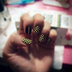Sally Hansen nail polish strips with black nail polish and yellow rhinestones