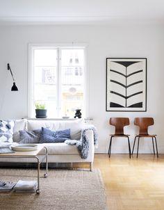 I vardagsrummet står en soffa från Eilersen. Soffbord Karin, design Bruno Mathsson, köpt på Blocket. Matta från Ikea. Vägglampan satt i Marias pappas garage. Tavlan är ett motiv av konstnären Anne Nilsson. Nedanför står två T-stolar, design Arne Jacobsen, Fritz Hansen.
