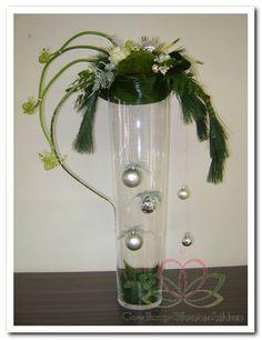 kerst-stuk op glazen vaas met oa kerstballen bloemen en takken