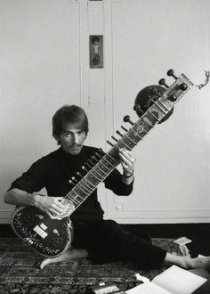 George Harrison, playing sitar