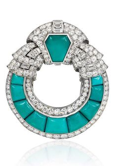 An Art Deco turquoise brooch of open circular design with scrolled diamond top and borders, in platinum. France circa 1925