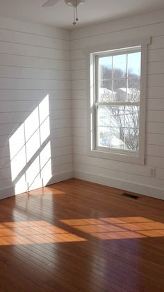 Faux shiplap walls with simple window trim and wood floors. Thinking about this for the living room.