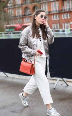 This stylish outfit works on the power of two - for every colour you introduce to the outfit, make sure you have two pieces in the hue. Her silver bomber and trainers, her cream two piece and her orange bag and phone case make matchy-matchy look very cool indeed