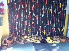 Cortinatge en cordes rústiques, robes, boles de paper maixé i ampolles trasparents plenes de paper de seda de colors de la tardor.