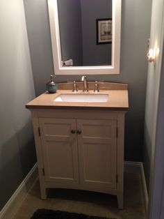 "Powder Room.  Had a small pedestal sink when we bought the condo, but soon realized when decorating ""small spaces"" you need storage space wherever you can get it!  Had vanity installed within the first month!  Vanity and mirror from Lowes.  Paint:  Benjamin Moore, HC 165 Boothbay Gray."