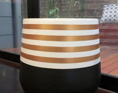SMALL lightweight plant pot hand painted in khaki and black with a metallic gold stripe. This is a striking design which will add a touch a glamour to your home! The material of the pot is fibreglass and painted using water-based and acrylic paints. Size is 25 x 25cm.  Our pots have their own personality and imperfections which is what makes them unique. As the pots are hand painted they are delicate and need to be handled with extra care. They are intended for indoor use or in a covered…