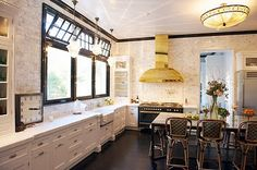 White cabinets, black window panes, louvered transoms, brass and black appliances, French rattan stools