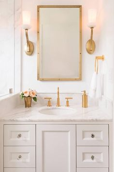 Gold fixtures on marble vanity with mirror and double sconces