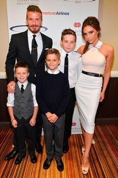 Victoria Beckham com a família toda em evento, veste vestido midi branco e peeptoe