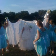 "The bridesmaids held vintage white table cloths and sang ""going to the chapel"" on the way to the alter."