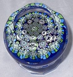A Superb Millefiori Piedouche or Pedestal paperweight with silhouette canes and facet cutting, by John Deacons who stands in a long tradition of paperweight making in Scotland and was greatly influenced by Salvador Ysart and his four sons, the most famous of whom was Paul. The Ysarts were a family of Spanish immigrants who all worked for the Moncrieff Glassworks in the 1920s and 1930s.