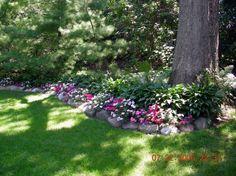 Hostas and impatiens with rock garden border -Add in ferns