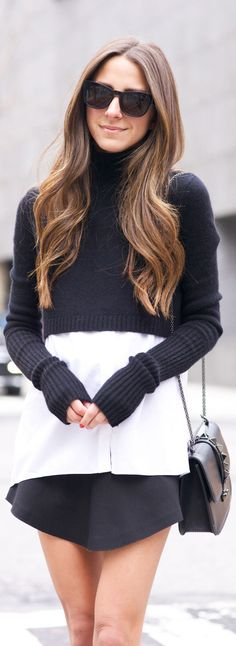 Via Just The Design: Arielle Nachami is wearing a cropped Elie Tahari turtleneck with a studded Valentino clutch bag and a black mini skirt