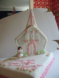 1st communion cake - This is an easy cake for a 1st communion. I used the wilton house pan for the church with a steeple made from white chocolate. It sits on top of a sheet cake with a store bought figure.