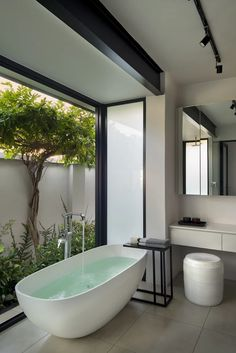 The new main bathroom is a locus of calm, with doors that fold away to reveal a secluded garden. The freestanding bath is from Dado Baths, and it's matched with an old side table of Hendrien's and a white ceramic stool by Anthony Shapiro. Outdoor Bathrooms, Dream Bathrooms, Beautiful Bathrooms, Modern Bathroom Design, Bathroom Interior Design, Interior Decorating, Interior Livingroom, Bathroom Layout, Minimalist Home