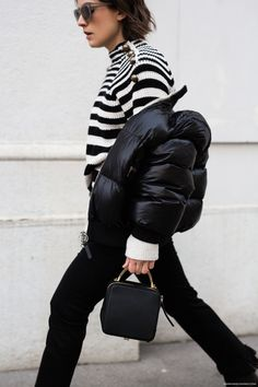 Black puffer jacket worn off the shoulder