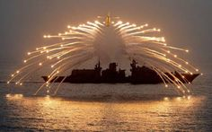 AWESOME MILITARY PICTURES - COMBAT HELICOPTER RELEASES DEFENSIVE ANGEL FLARES WITH NAVAL WARSHIP IN BACKGROUND!