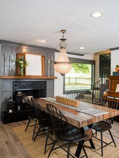 Dark gray paneling around the fireplace provides visual contrast with the light walls. Limitations in the renovation budget precluded adding larger windows, but the existing windows were updated with new trim also painted in gray.