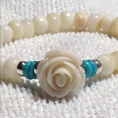 Pearl and genuine turquoise bracelet This lovely piece is made with freshwater pearls in a soft shade of beige. Genuine turquoise on either side of the white rose gives the bracelet a nice little pop of color. The spacers are .925 sterling silver. This is elastic for a comfortable fit. Jewelry Bracelets