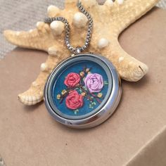 This is so cool! Pretty silk ribbon rose hand embroidery in a glass locket. Makes a great gift and complements any outfit.      https://www.etsy.com/listing/247624393/embroidered-necklace-embroidery-jewelry