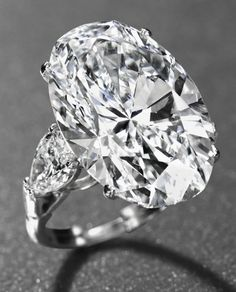 AN IMPORTANT DIAMOND RING, BY GRAFF. Set with an oval-shaped diamond, weighing approximately 26.24 carats, to the pear-shaped diamond shoulders, weighing approximately 1.06 and 1.04 carats, in platinum...