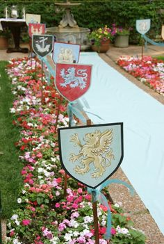 Ceremony aisle decor by Design Come True, artist Allison Cosmos. Each coat of arms is hand painted.