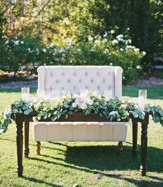 Wedding sweetheart table ideas. Using a high back tufted sofa is not only romantically elegant but frames you two in photos! Add dark wood farm table as contrast. Lots of lush full floral completes your wedding day look