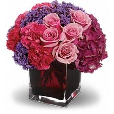 "Romance that stands all the tests of time is like an enchanted journey. This beautiful arrangement is a wonderful way to celebrate that love. Gorgeous dark pink hydrangea, pink roses and carnations, plus lavender statice are lovingly arranged in an exclusive plum-colored cube vase. Approximately 9"" W x 9"" H"
