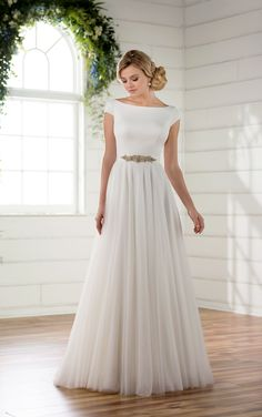 Make a unique statement in this modest luxe boho wedding dress from Essense of Australia. Featuring a structured Crepe bodice, this gown boasts sweet cap sleeves and a boat neckline that extends effortless into a romantic scoop back giving a modest and elegant look. A detachable beaded belt highlights the waist before extending into a soft, French Tulle skirt and train. The back of this lightweight and boho-inspired gown zips up beneath fabric buttons. Available in plus sizes.