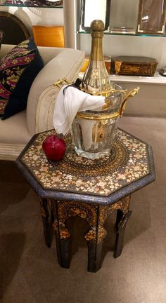 """An apple a day keeps the doctor away... pretty sure champagne does too. On an exquisite Kashmir folding octagonal table c.1910, the Ice bucket is a rather glitzy Baccarat model called """"Moulin Rouge""""."""