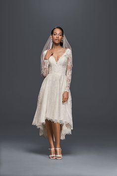 A short lace wedding dress from Oleg Cassini that's absolutely gorgeous. The high-low skirt and V-neckline are trimmed in scalloped lace, and the long sleeves feature illusion lace. Exclusively at David's Bridal.