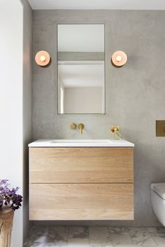 The master bathroom walls are finished in gray tadelakt. The plumbing fixtures are Vola and the sconces are Trapeze from NYC's Apparatus Studio.