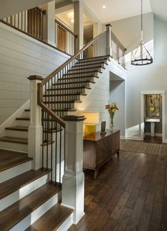 Entryway with rustic wood floors, L-shaped stairway, shiplap wall, rustic chandelier   Charlie & Co. Design, Ltd