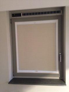 Geplisseerde gordijnen in een frame op een draai/kiep raam gemonteerd