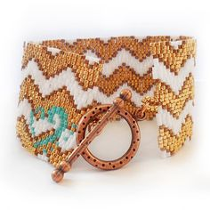 Feel Elegant and Sexy with this New chevron bracelet handmade with an original dicopebisuteria design with best quality glass beads in white , gold and bronze colors ! An exquisite jewel of more than a 2500 beads ( with 8 hours of work ) and an easy to use copper toggle clasp.  You will shine with this bracelet !! Perfect to be the most elegant of the party !  ♥ This bracelet its 7 inches long and 1,5 wide, its 18 cm long and 3,8 cm width  ♥ Ready to ship !  ♥ Do you like it ? Click the…