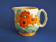 A small Paris shape jug produced by Gray s around 1930 Boldly painted art deco flowers in red orange and yellow with blue and green detail in a style