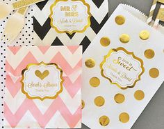 Girl baby shower party favor boxes will make sweet baby girl favors! Shiny metallic gold foil labels can be customized with a design to match your event - even a pink and gold theme baby shower. These uniquely shaped favor boxes come complete with a convenient handle when assembled. Fill them with candies, cookies, or your other favorite goodies for an unforgettable party favor that your guests are sure to enjoy!  CHOCOLATES AND CANDY NOT INCLUDED. BOXES ARE EMPTY.  Boxes ship flat and…