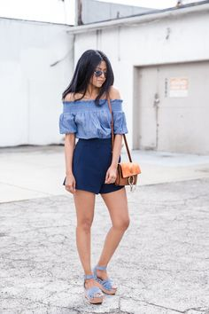 A chambray off-the-shoulder top tucked into navy shorts and platform sandals