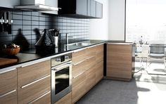 Modern wood finish IKEA kitchen with dark worktops, dark wall cabinets and integrated appliances