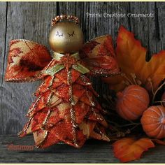"""Autumn is a quilted wired ribbon angel made with a beautiful autumn leaves ribbon with gold edging. She has wings made of the same ribbon and a beaded halo of gold and copper. Autumn stands 4 1/2"""" tall and can be hung by the gold ribbon hanger or the hanger can be removed and she will stand on a shelf or table."""