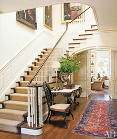 Love the casualness of the old dhourrie in the hall and the double trimmed sisal stair runner contrasted with the big brass lantern and the gilt framed large portraits.