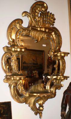 Espejo con marco y con estantes en madera tallada y dorada. Estilo Rococó, mitad del siglo XIX. 94 x 58 cm.