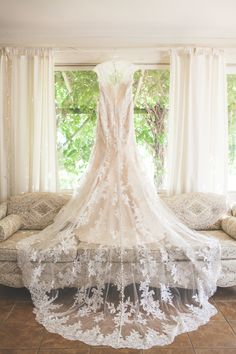 Lace train wedding dress hanging up in the farm house. Full button wedding dress. Photography by Brittania Drew.