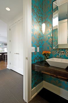 Nice alternative to a pedestal sink: wood plank with ceramic bowl. Bright turquoise wallpaper