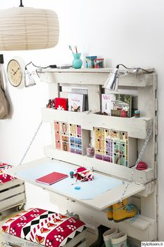 pallet fold up desk and crate repurposed into a cushioned rolly bench.
