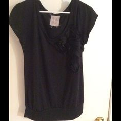 Black shirt with flower Black shirt never worn has a flower on the front and band at the bottom. Super cute Tops
