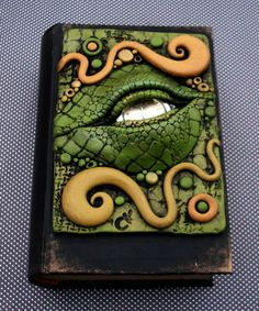 I decorated the cover of this little book box (looks like a book but is hollow) with a polymer clay design that includes a watch for the dragons eye. Watch faces work great as they reflect light an. Polymer Clay Projects, Polymer Clay Art, Biscuit, Dragon Eye, Clay Dragon, Halloween Books, Clay Design, Magic Book, Paperclay