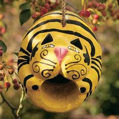 Whimsical birdhouse carved out of coconut shell and painted like a kitty